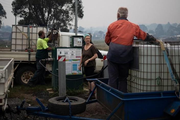 Kim Green fills a tank with water to protect his farm from a possible bushfire as his wife Sherenee stands by, in the town of Eden