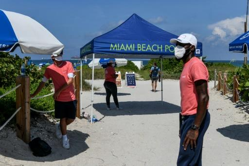 """Social distancing ambassadors"" stand at the entrance to Miami Beach on June 10"