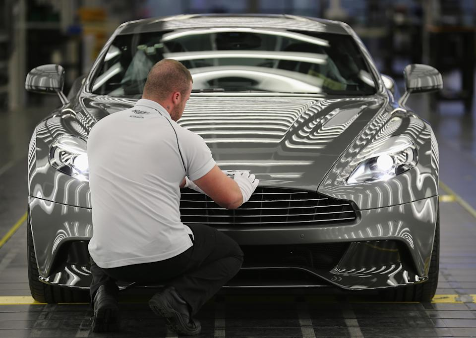 GAYDON, ENGLAND - JANUARY 10:  An Aston Martin Vanquish is inspected by hand inside a light booth at the company headquarters and production plant on January 10, 2013 in Gaydon, England. The iconic British brand is celebrating its 100th anniversary. Lionel Martin and Robert Bamford created Bamford & Martin on January 15 1913, which later became Aston Martin in honour of Bamford's wins at the Aston Clinton Hillclimb in Buckinghamshire.  (Photo by Christopher Furlong/Getty Images)