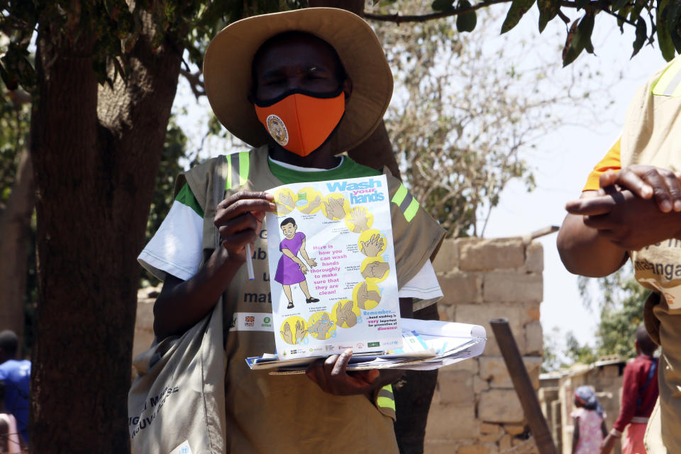 A community health worker holds a pamphlet during a COVID-19 awarness campaign in Chitungwiza on the outskirts of Harare, Wednesday, Sept. 23, 2020. As Zimbabwe's coronavirus infections decline, strict lockdowns designed to curb the disease are being replaced by a return to relatively normal life. The threat has eased so much that many people see no need to be cautious, which has invited complacency. (AP Photo/Tsvangirayi Mukwazhi)
