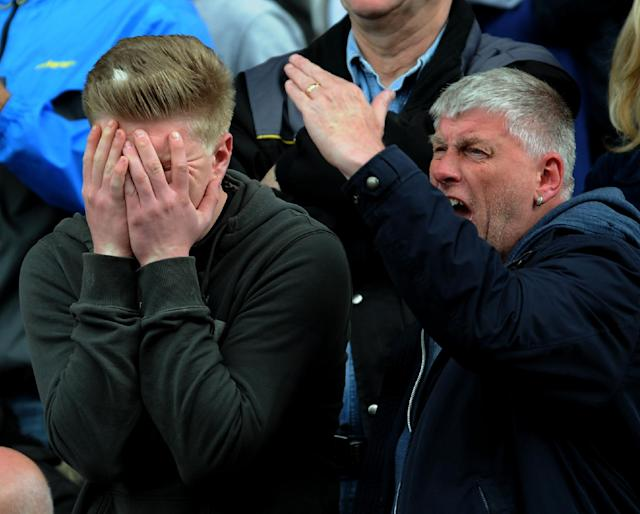 Fulham fans react as their team is relegated after losing 4-1 to Stoke City during the English Premier League soccer match between Stoke City and Fulham at the Britannia Stadium in Stoke On Trent, England, Saturday, May 3, 2014. (AP Photo/Rui Vieira)