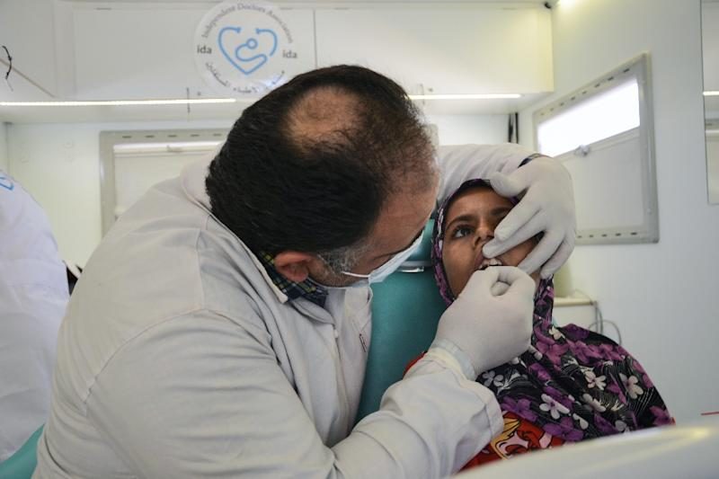 Muhanned Qabtur, a Syrian dentist, operates on a patient inside a vehicle which has been converted into a mobile dental clinic (AFP Photo/Nazeer al-Khatib)
