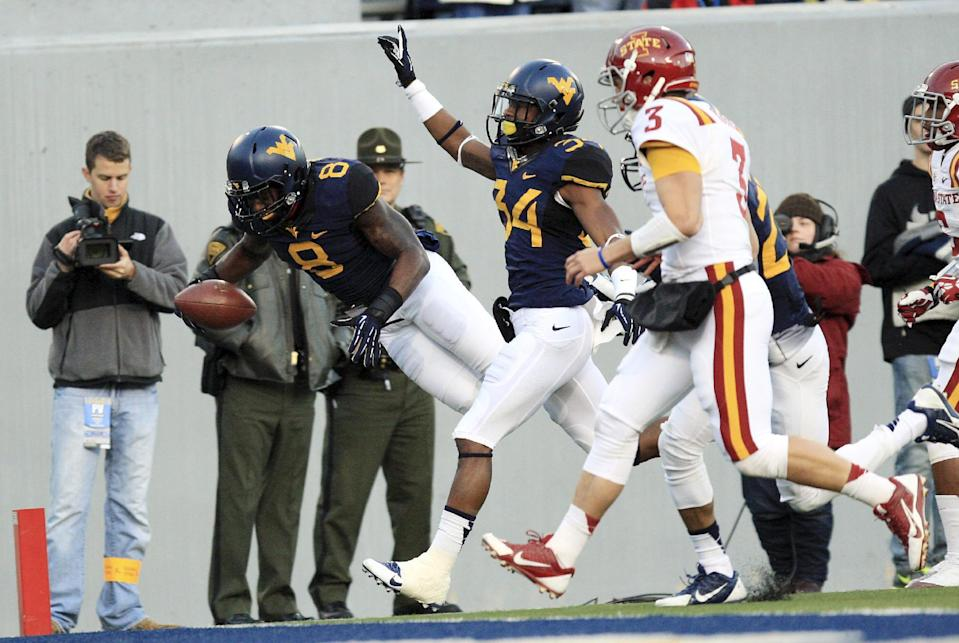 West Virginia's Karl Joseph (8) jumps in for a touchdown after picking up a fumble during the first quarter of an NCAA college football game against Iowa State in Morgantown, W.Va., on Saturday, Nov. 30, 2013. (AP Photo/Christopher Jackson)