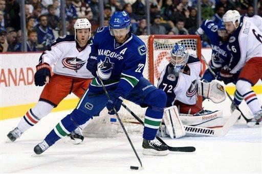 Vancouver Canucks' Daniel Sedin protects the puck in front of Columbus Blue Jackets goalie Sergei Bobrovsky and defenseman Dalton Prout during the first period of an NHL hockey game in Vancouver, British Columbia, Tuesday, March 26, 2013. (AP Photo/The Canadian Press, Jonathan Hayward)