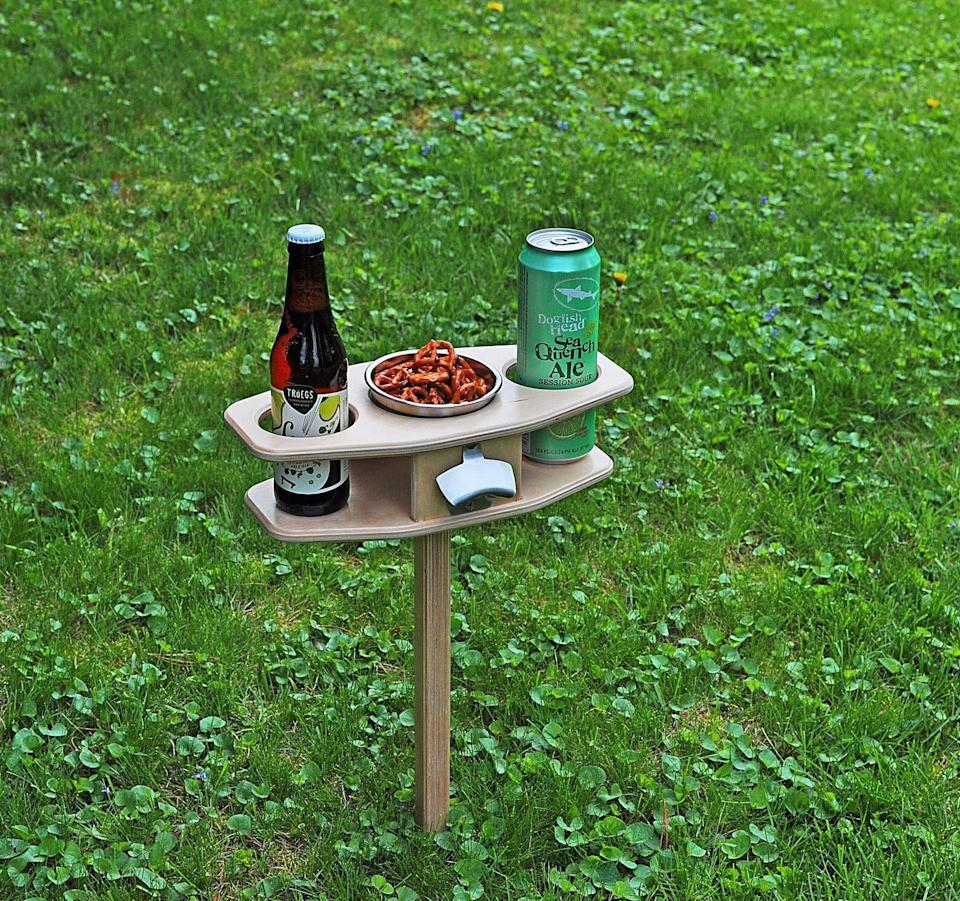 """Let's raise one for this table. <a href=""""https://www.etsy.com/listing/608072063/outdoor-beer-table-collapsible-beer?ga_order=most_relevant&amp;ga_search_type=all&amp;ga_view_type=gallery&amp;ga_search_query=wine+table+outdoor&amp;ref=sr_gallery-1-7&amp;organic_search_click=1&amp;frs=1&amp;bes=1"""" rel=""""nofollow noopener"""" target=""""_blank"""" data-ylk=""""slk:Find it for $58 on Etsy"""" class=""""link rapid-noclick-resp""""> Find it for $58 on Etsy</a>."""