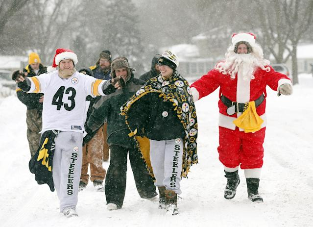 Fans make their way through some snow to Lambeau Field before an NFL football game between the Green Bay Packers and the Pittsburgh Steelers Sunday, Dec. 22, 2013, in Green Bay, Wis. (AP Photo/Jeffrey Phelps)