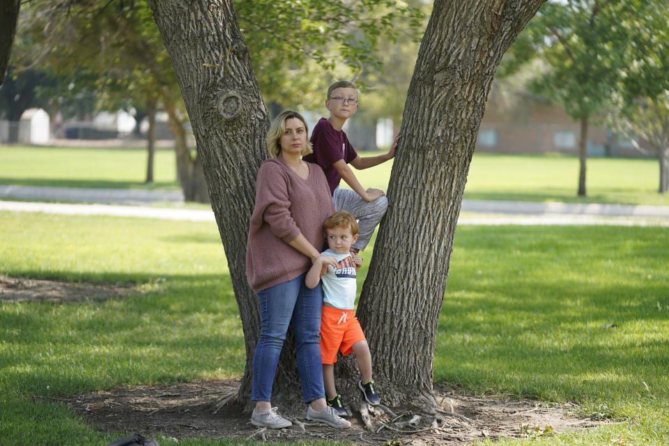 Jessica Pyper poses for a photograph with her children Ryker, 10, and Sage, 3, on Friday, Aug. 20, 2021, in West Jordan, Utah. A group of Utah parents is suing the state over a law that bans school districts from approving mask mandates. It's the latest U.S. legal challenge over rules for face coverings in the classroom. (AP Photo/Rick Bowmer)