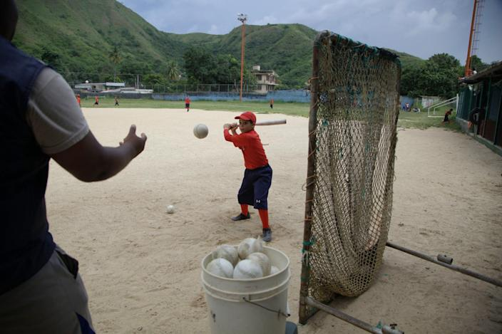 In this Oct. 25, 2012 photo, a young player practices batting at a baseball school in Maracay, Venezuela. Many of the boys are inspired by the example of Detroit Tigers slugger Miguel Cabrera, who learned the game on this very field. Their baseball school in the poor neighborhood where Cabrera grew up is one of many across Venezuela, a web for training young ballplayers that has made the country a powerhouse in the U.S. major leagues. (AP Photo/Ariana Cubillos)