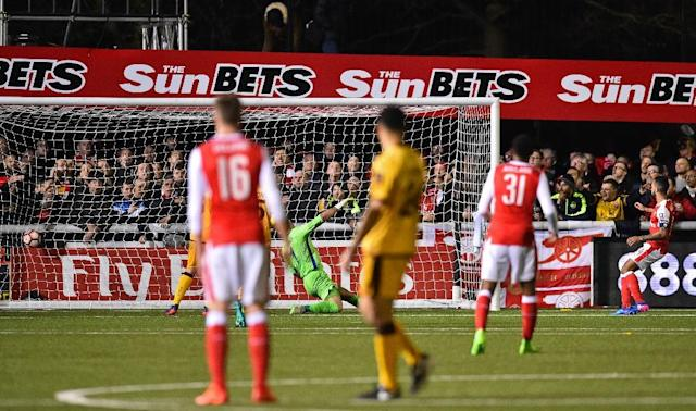 Arsenal's English midfielder Theo Walcott (R) watches his shot as he scores their second goal, his 100th goal for Arsenal, during the English FA Cup fifth round football match between Sutton United and Arsenal on February 20, 2017 (AFP Photo/Glyn KIRK)