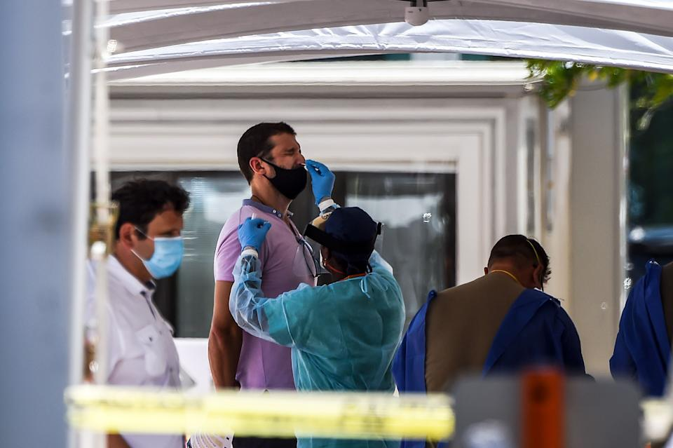 """A medical personnel member takes samples on a man at a """"walk-in"""" and """"drive-through"""" coronavirus testing site in Miami Beach, Florida on June 24, 2020. - With coronavirus cases surging across the US South and West, officials are once again imposing tough measures, from stay-at-home advice in worst-hit states to quarantines to protect recovering areas like New York. Nearly four months after the United States reported its first death from COVID-19, the nation faces a deepening health crisis as a wave of infections hits young Americans and experts issue new acute warnings. (Photo by CHANDAN KHANNA / AFP) (Photo by CHANDAN KHANNA/AFP via Getty Images)"""