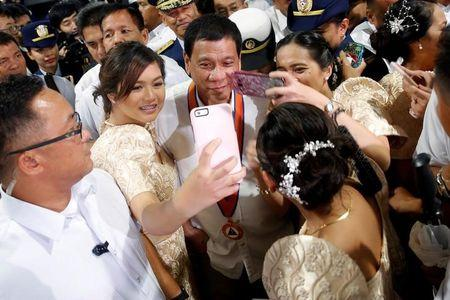 Philippines President Rodrigo Duterte has his pictures taken with women as they attend the ceremony marking the anniversary of the Philippines Coast Guard in Manila, Philippines, October 12, 2016. REUTERS/Damir Sagolj/Files