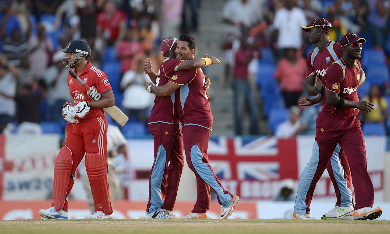 ANTIGUA, ANTIGUA AND BARBUDA - FEBRUARY 28:  Ravi Bopara of England leaves the field as Dwayne Bravo and Ravi Rampaul of the West Indies celebrates winning the 1st One Day International between West Indies and England at Sir Viv Richards Cricket Ground on February 28, 2014 in Antigua, Antigua and Barbuda.  (Photo by Gareth Copley/Getty Images)