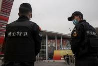 Security keep watch as WHO team members visit an exhibition on how China fought the coronavirus in Wuhan