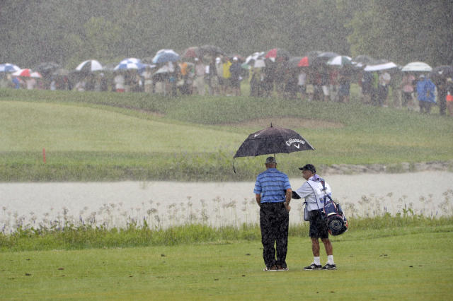 Jim Furyk, of the United States, takes cover under an umbrella during final-round action at the Canadian Open golf championship in Montreal, Sunday, July 27, 2014. (AP Photo/The Canadian Press, Ryan Remiroz)