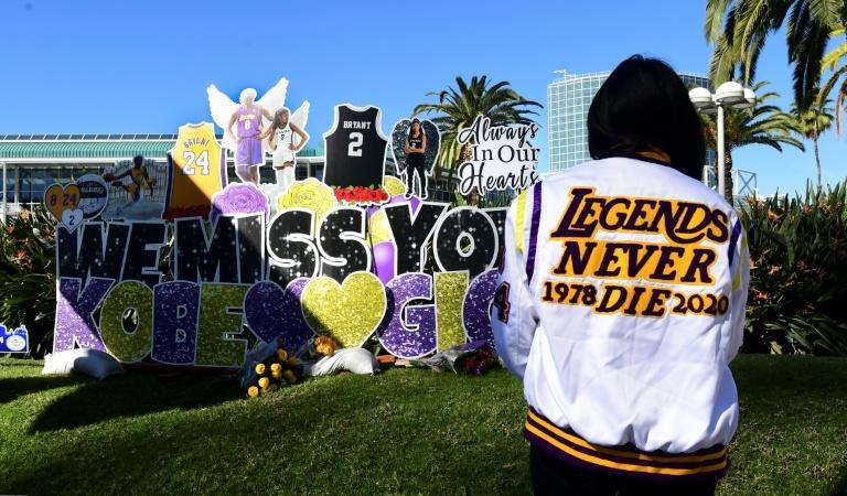 """Lakers fan Bree Rodriguez wears a jacket with words """"Legends Never Die"""" as she visits a memorial to Kobe Bryant on Monday near the Staples Center in Los Angeles, one-year after the NBA icon's death"""
