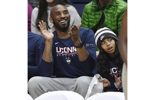 In this March 2, 2019 photo, Kobe Bryant and his daughter Gianna watch the first half of an NCAA college basketball game between Connecticut and Houston in Storrs, Conn. Dads with daughters inspired by Kobe Bryant's special bond with his 13-year-old Gianna took to social media to celebrate their own daughters in words and photos using the hashtag #GirlDads. Bryant and his daughter died in a helicopter crash on Sunday, Jan. 26, 2020. (AP Photo/Jessica Hill)