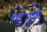 Toronto Blue Jays' Russell Martin, left, is congratulated by Justin Smoak after hitting a three-run home run off Oakland Athletics' Kendall Graveman during the sixth inning of a baseball game Tuesday, July 21, 2015, in Oakland, Calif. (AP Photo/Ben Margot)