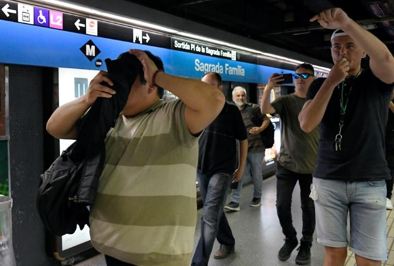 Citizens on patrol use whistles to warn metro passengers of a presumed pickpocket (L) in Barcelona where there has been a surge in muggings and burglaries (AFP Photo/LLUIS GENE)