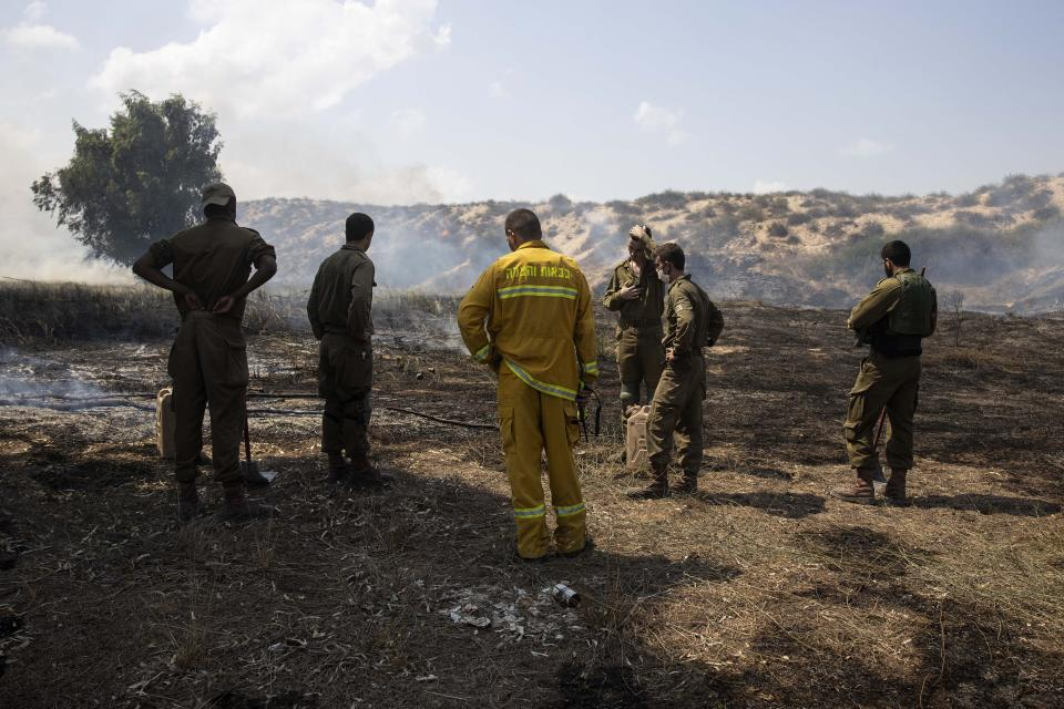 Israeli soldiers and a firefighter examine a fire started by an incendiary device launched from the Gaza Strip, on the Israeli side of the border between Israel and Gaza, near Kibbutz Netiv Ha'asara, Wednesday, Aug. 12, 2020. The Israeli military said it attacked a number of Hamas targets in the Gaza Strip early Wednesday in response to days of launches of explosives-laden balloons from Gaza into Israeli territory. Israel says it holds Gaza's Hamas rulers responsible for all fire emanating from the territory. (AP Photo/Tsafrir Abayov)