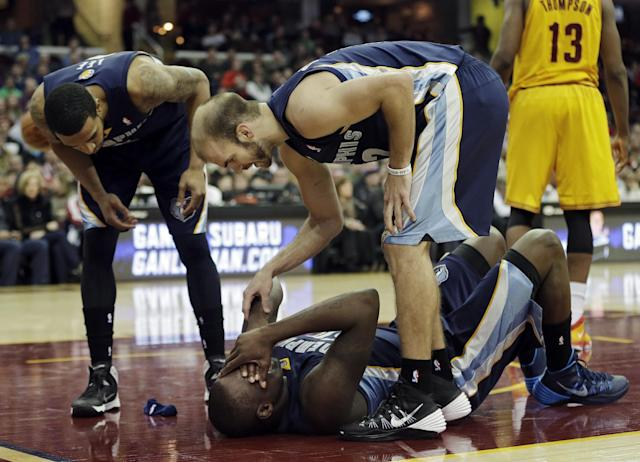 Memphis Grizzlies' Courtney Lee, left, and Nick Calathes, right, look over teammate Zach Randolph after an injury in the second quarter of an NBA basketball game against the Cleveland Cavaliers, Sunday, Feb. 9, 2014, in Cleveland. (AP Photo/Mark Duncan)