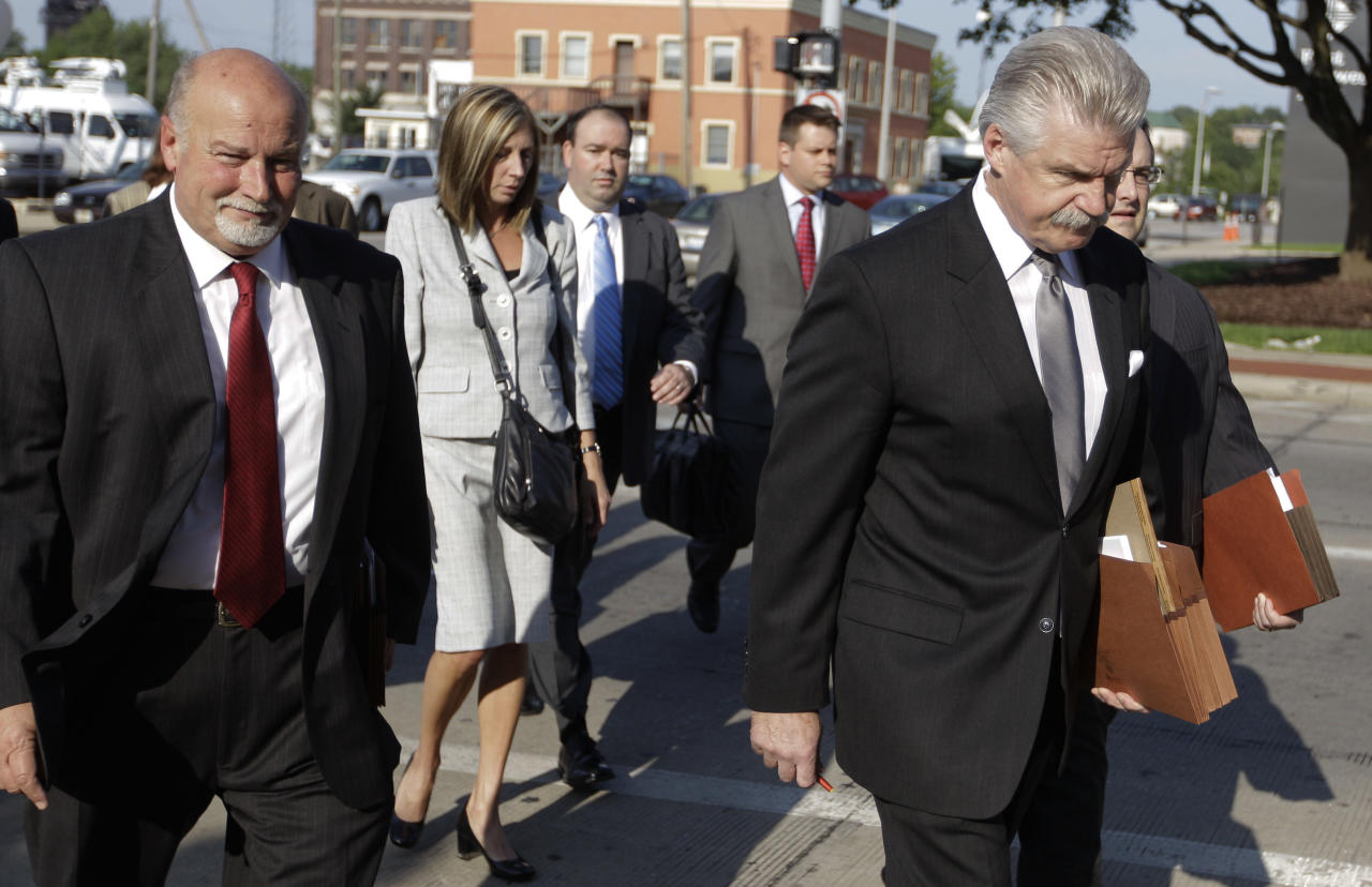 Will County State's Attorney James Glasgow, right, leads his team into court for the first day of jury selection in Drew Peterson's murder trial, Monday, July 23, 2012, in Joliet, Ill. Peterson, 58, is charged with killing his third wife, Kathleen Savio, in 2004. Her body was found in a dry bathtub in her home, her hair soaked with blood. The ex-Bolingbrook police sergeant is also a suspect in the 2007 disappearance of his fourth wife, Stacy Peterson. (AP Photo/M. Spencer Green)