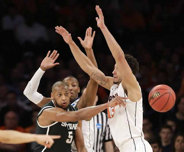 Michigan State's Adreian Payne passes the ball around Virginia's Anthony Gill during the second half of a regional semifinal at the NCAA men's college basketball tournament, Friday, March 28, 2014, in New York. (AP Photo/Seth Wenig)