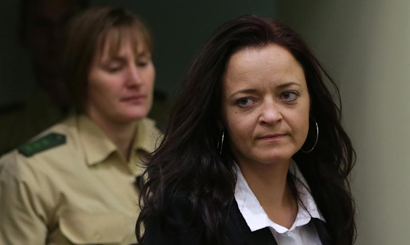 FILE - In this June 11, 2013 file picture Beate Zschaepe,, right, alleged member of the neo-Nazi group National Socialist Underground, NSU, enters a court room in Munich, southern Germany, A nearly 1,400-page report released Thursday Aug. 22, 2013 follows a 19-month review of how police and intelligence agencies failed to stop the National Socialist Underground group killing eight Turks, a Greek and a policewoman between 2000 and 2007. The group was only linked to the killings after two main members died in a murder-suicide after a botched 2011 bank robbery. The third suspected main member is now on trial. The cross-party committee says authorities didn't properly consider the possibility that the killings were racially motivated, partly because of their own biases. It calls for more minorities in the security services. (AP Photo/Matthias Schrader, File)