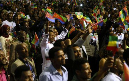 Residents wave the Ethiopian and Eritrean national flags as they dance during a concert at the Millennium Hall in Addis Ababa, Ethiopia July 15, 2018. REUTERS/Tiksa Negeri