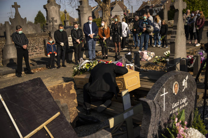 A relative of Margodt Genevieve, who died due to Covid-19, grieves over her coffin during her funeral ceremony at the Montignies cemetery in Charleroi, Belgium, Wednesday, April 8, 2020. The new coronavirus causes mild or moderate symptoms for most people, but for some, especially older adults and people with existing health problems, it can cause more severe illness or death. (AP Photo/Francisco Seco)