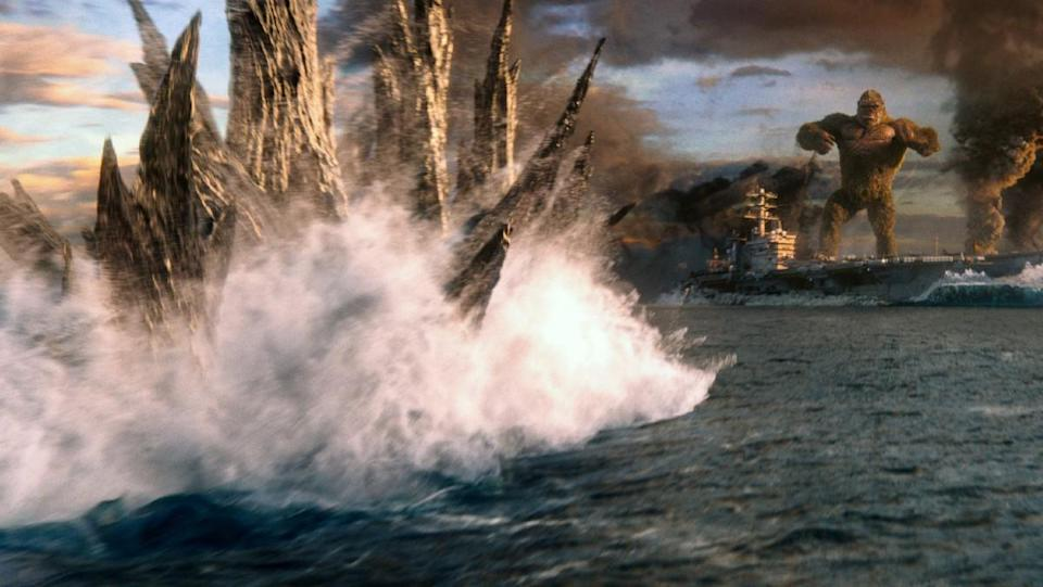Godzilla swims through the ocean approaching a boat where King Kong stands in a scene from Godzilla vs. Kong.
