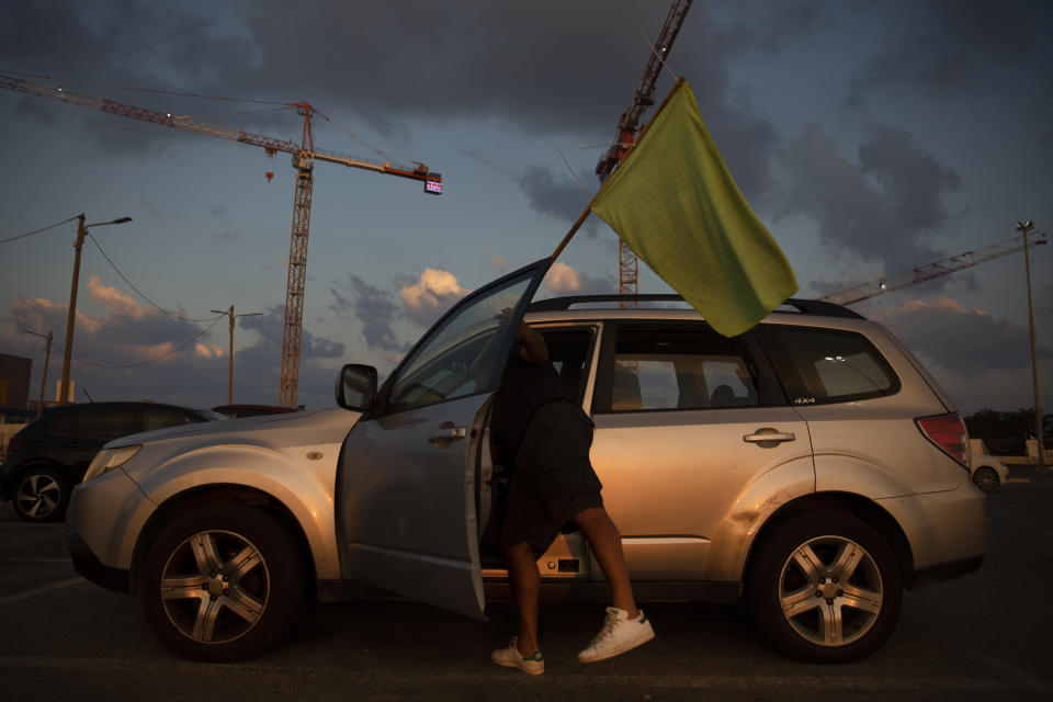 """A man places a green flag on his car as he prepares to join a convoy of cars and protest against the Health Ministry's """"green pass"""" restrictions, in Tel Aviv, Israel, Sunday, Oct. 3, 2021. Israel restricted its coronavirus """"green pass"""" on Sunday to allow only those who have received a COVID-19 booster or recently recovered to enter indoor events, sparking protests by opponents who say the system is a form of forced vaccination. AP Photo/Oded Balilty)"""