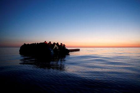 FILE PHOTO: Migrants on a rubber dinghy await rescue by the Malta-based NGO Migrant Offshore Aid Station (MOAS) at dawn in the central Mediterranean in international waters