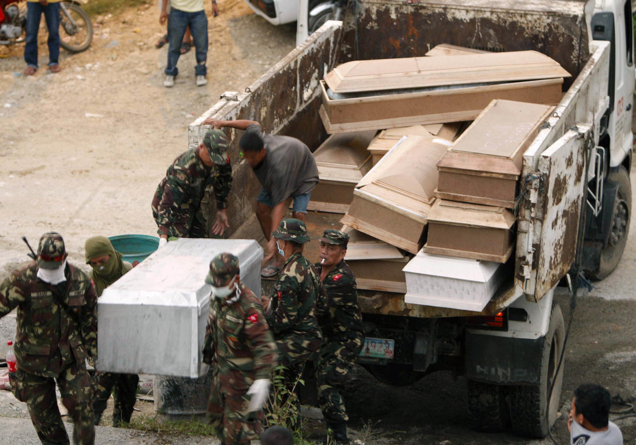Soldiers carry coffins of flash flood victims during a mass burial Tuesday Dec. 20, 2011 at a public cemetery in Iligan city in southern Philippines. Dozens of grieving relatives of the victims wept openly during funeral rites presided by a Catholic bishop at nightfall in Iligan city. (AP Photo/Bullit Marquez)