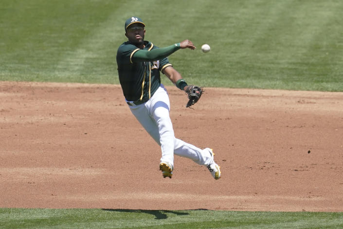 Oakland Athletics shortstop Elvis Andrus throws to first base on a single hit by Texas Rangers' Nick Solak during the second inning of a baseball game in Oakland, Calif., Thursday, July 1, 2021. (AP Photo/Jeff Chiu)