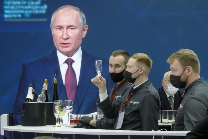Waiting staff prepare to distribute soft drinks for journalists gathered in the press center to listen to Russian President Vladimir Putin address at the St. Petersburg International Economic Forum in St. Petersburg, Russia, Friday, June 4, 2021. (AP Photo/Dmitri Lovetsky)
