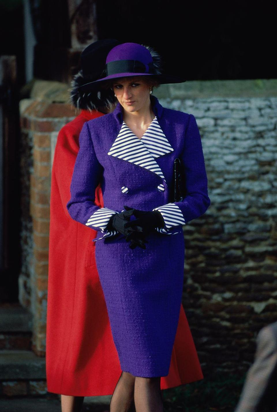 <p>Diana eschewed traditional Christmas Day coloring for this deep purple tuxedo dress, accented with striped detailing.</p>