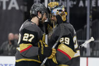Vegas Golden Knights goaltender Marc-Andre Fleury (29) and defenseman Shea Theodore (27) celebrate after the Vegas Golden Knights defeated the Montreal Canadiens in Game 1 of an NHL hockey Stanley Cup semifinal playoff series Monday, June 14, 2021, in Las Vegas. (AP Photo/John Locher)