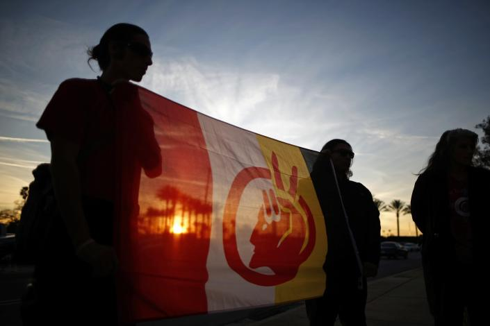 People holding the American Indian movement flag protest against the Keystone XL Pipeline, which would carry petroleum from Canada to refineries in Texas, outside WorleyParsons engineering consultancy company in Arcadia, California January 14, 2015. The U.S. Senate advanced a bill on Monday to approve the pipeline as Republicans, who have made the project their first priority of the year, try to line up enough votes to overcome a potential veto by President Barack Obama. REUTERS/Lucy Nicholson (UNITED STATES - Tags: ENVIRONMENT CIVIL UNREST ENERGY BUSINESS SOCIETY)