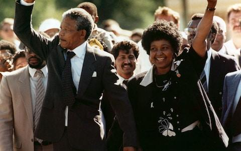 Nelson Mandela and his wife, Winnie, walking hand in hand, raise clenched fists upon Mandela's release from Victor Verster Prison, in Paari, South Africa