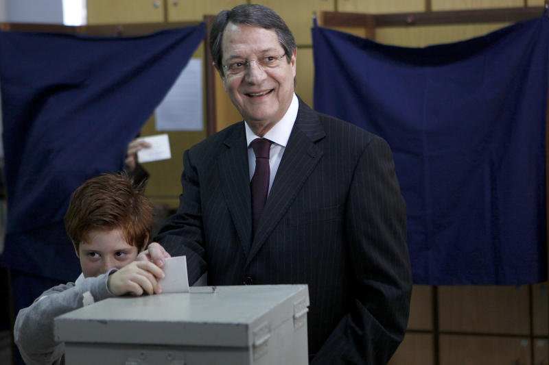 Opposition party leader and presidential candidate Nicos Anastasiades votes with his grandson Andis, in the Presidential election in southern port city of Limassol, Cyprus, Sunday, Feb. 24, 2013. Faced with the specter of financial meltdown, Cypriots are choosing a new president with the conservative candidate favored to win over his left-wing rival in a runoff vote Sunday.(AP Photo/Petros Karadjias)