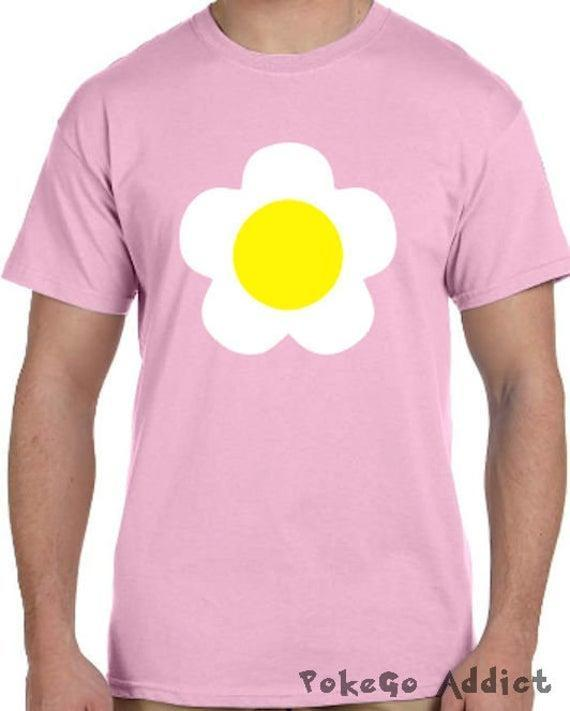 """<h2>Villager Girl Shirt</h2><br>This Uni-sex flower top is a perfect replica of the original default Animal Crossing Villager girl. Throw on a pink wig and you're set. Plus, this piece will make grade-A sleep shirt material for AC superfans long after Hallo's eve.<br><br><em>Shop</em> <strong><em><a href=""""https://www.etsy.com/shop/httpkoopa"""" rel=""""nofollow noopener"""" target=""""_blank"""" data-ylk=""""slk:httpkoopa"""" class=""""link rapid-noclick-resp"""">httpkoopa</a></em></strong> <br><br><strong>PokeGoAddict</strong> Villager Girl Animal Crossing Cosplay T-Shirt, $, available at <a href=""""https://go.skimresources.com/?id=30283X879131&url=https%3A%2F%2Fwww.etsy.com%2Flisting%2F470481928%2Fvillager-girl-animal-crossing-cosplay"""" rel=""""nofollow noopener"""" target=""""_blank"""" data-ylk=""""slk:Etsy"""" class=""""link rapid-noclick-resp"""">Etsy</a>"""
