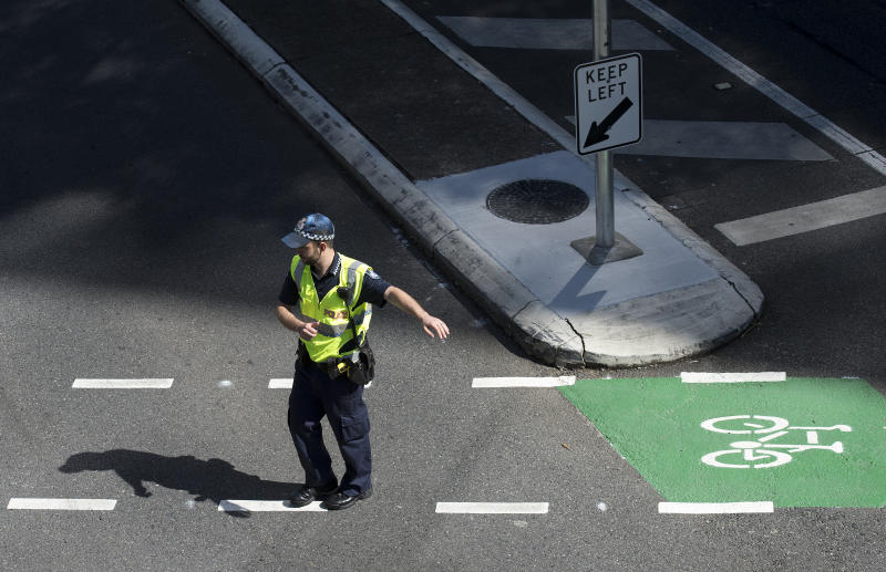 A police officer is seen directing traffic in the Brisbane CBD.