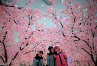Visitors pose for pictures at the Sunac Snow Centre in China's southwestern Sichuan province