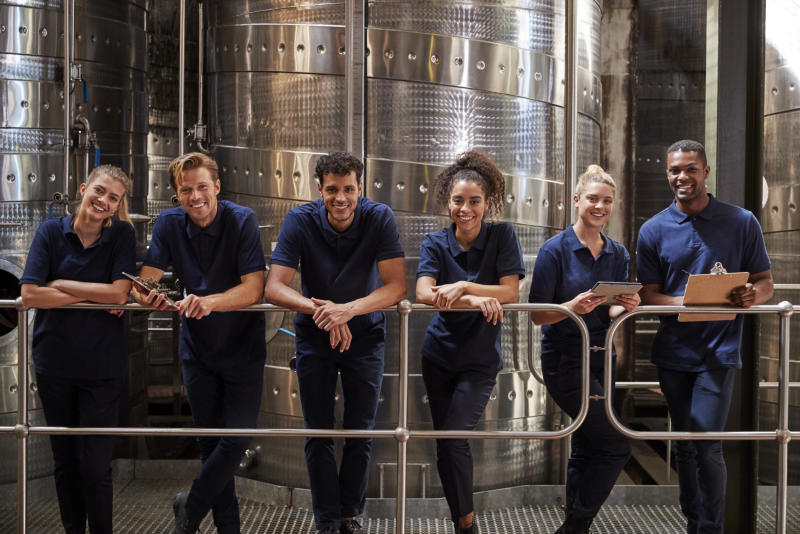 Winery staff in matching uniforms posing in front of a large steel vat.