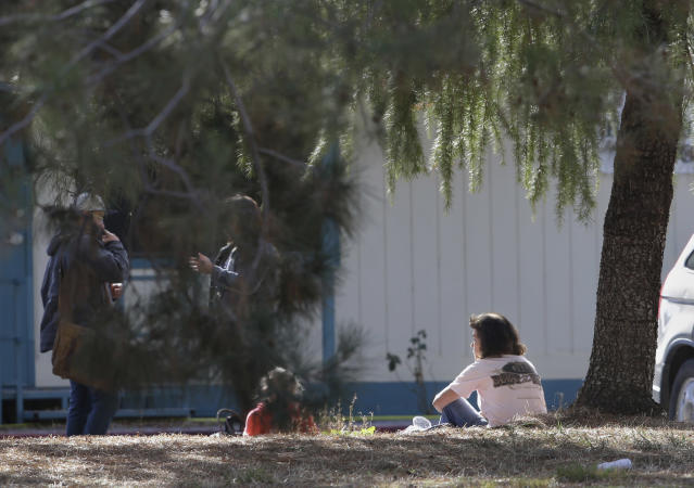 <p>A woman and a child sit by an elementary school where a gunman opened fire in the community of Rancho Tehama Reserve in Corning, Calif., Tuesday, Nov. 14, 2017. The gunman choosing targets at random opened fire in the rural Northern California town Tuesday, killing several people at several sites and wounding others at the elementary school before police shot him dead, authorities said. (AP Photo/Rich Pedroncelli) </p>