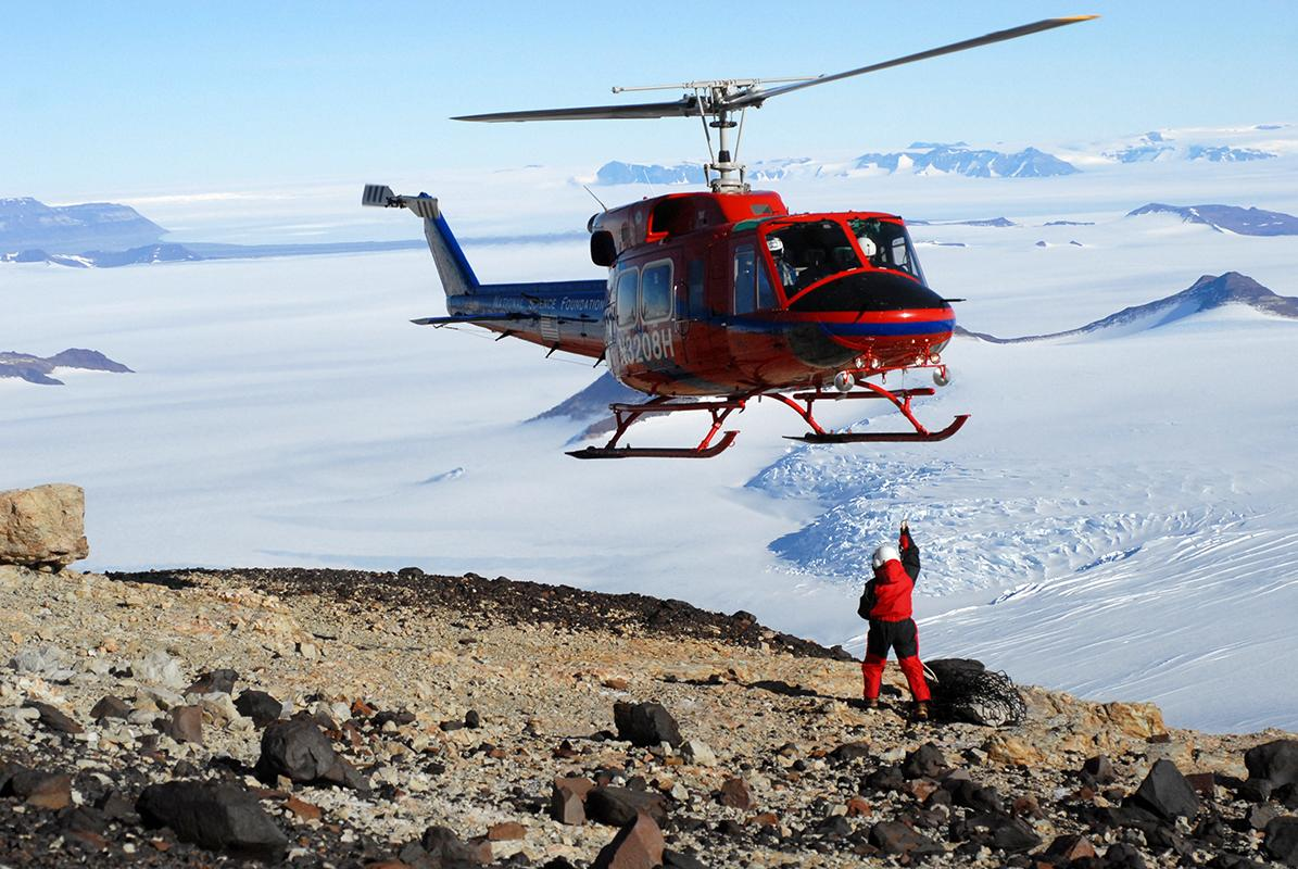 A helicopter prepares to transport fossil cargo over the ice and back to the Field Museum paleontologists' field camp, at the Beardmore Glacier in Antarctica.