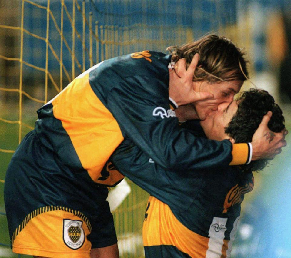 FILE - In this July 14, 1996 file photo released by Telam, Boca Juniors' Diego Maradona, right, and teammate Claudio Caniggia kiss as they celebrate Caniggia's goal, their team's second against River Plate, before their 4-1 victory in Buenos Aires, Argentina. The Argentine soccer great who was among the best players ever and who led his country to the 1986 World Cup title before later struggling with cocaine use and obesity, died from a heart attack on Wednesday, Nov. 25, 2020, at his home in Buenos Aires. He was 60. (Telam via AP File)