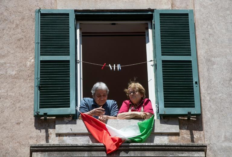 People stand at their window by the Italian flag in Rome on the anniversary of Liberation Day, which marks the fall of Nazi occupation in 1945