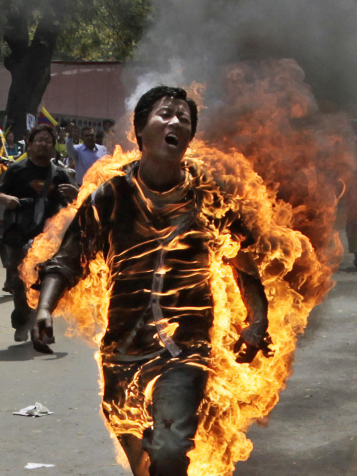 A Tibetan man, identified as Jampa Yeshi, screams as he runs engulfed in flames after self-immolating at a protest in New Delhi, India, ahead of Chinese President Hu Jintao's visit to the country Monday, March 26, 2012. The Tibetan activist lit himself on fire at the gathering and was rushed to hospital with unknown injuries, reports said. (AP Photo/Manish Swarup)