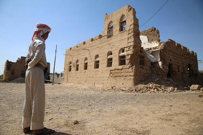 A Yemeni man stands next to a building destroyed in clashes between fighters from the Popular Resistance Committees and Shiite Huthi rebels in the village of Faw on the road to Marib province, on October 14, 2015 (AFP Photo/Abdullah al-Qadry)